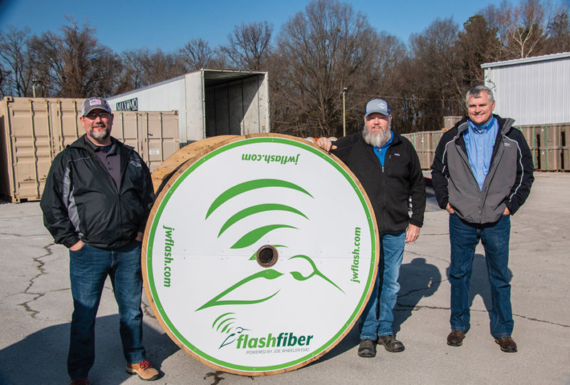 JW FlashFiber employees with giant spool of wire